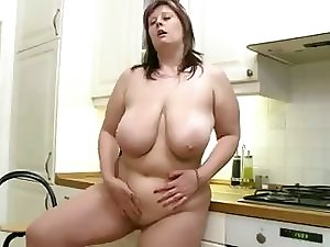 Weighty lascivious young lady with heavy tits masturbates in the kitchen.